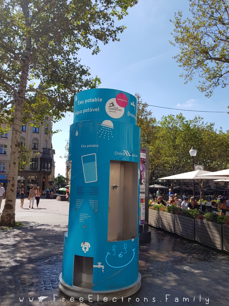 A FREE light-blue-colored water station for people and dogs in a pedestrian city square in Luxembourg.  Text on picture reads: www.FreeElectrons.Family.