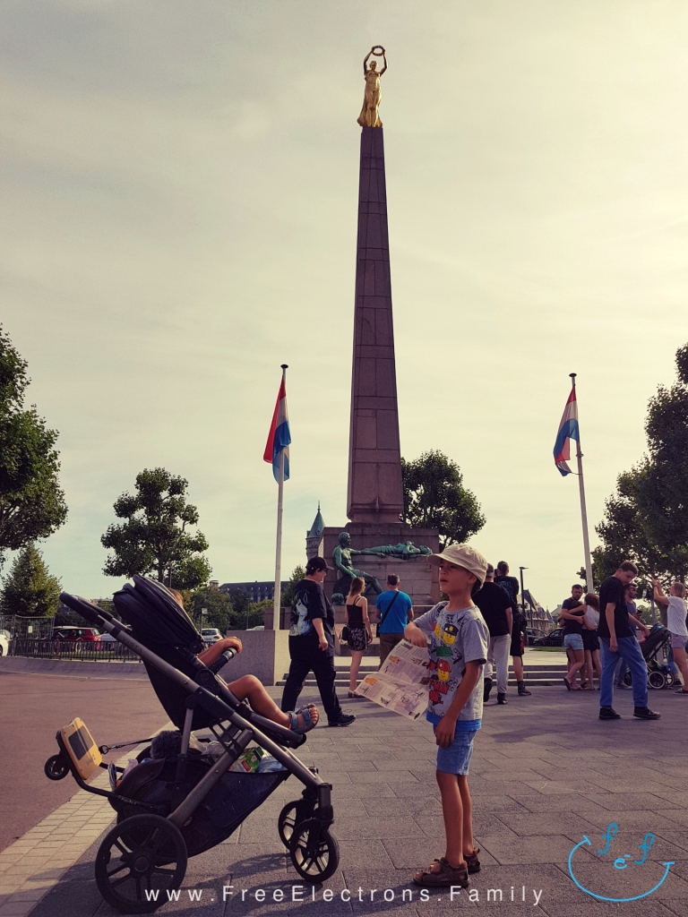 Two young boys (one standing, the other on a stroller/pram), in front of an obelisk monument with a golden statue on top at a pedestrian plaza, under gray sky with an inserted smiley face (custom icon) at the bottom corner.  Text on picture reads: www.FreeElectrons.Family