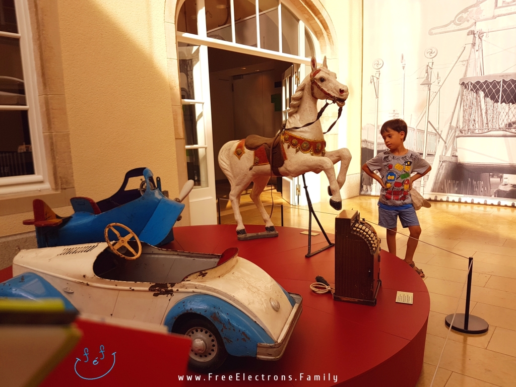 Old children toys (airplane, horse, car and a cash register) inside the Leutzebuerg/Luxembourg City Museum.  Text on picture reads: www.FreeElectrons.Family with an inserted smiley face (custom icon) at the bottom corner.
