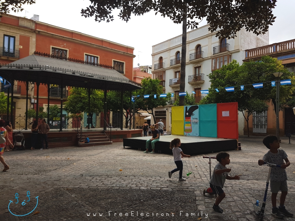 Children playing while waiting for an outdoor puppet show in a Spanish plaza, under cloudy skies.  Caption reads:  Waiting for the puppet show at Plaza del Banco, Jerez de la Frontera, International Puppet Festival (Festival Internacional de Títeres) in Septembers.  www.FreeElectrons.Family - what to do see in Jerez in September.