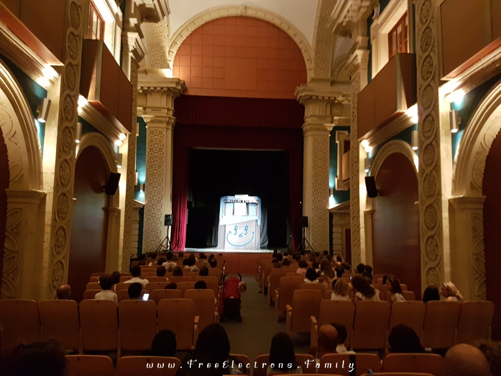 Indoor puppet show at an well-preserved historic theatre.  Caption reads:  The show must go on! In case of rain, the puppet shows would stay on schedule but move to indoor locations.  In this case. . . to Sala Compania (theater in the historic center of Jerez)... for the International Puppet Festival (Festival Internacional de Títeres) in September.  www.FreeElectrons.Family - what to do see in Jerez in September.