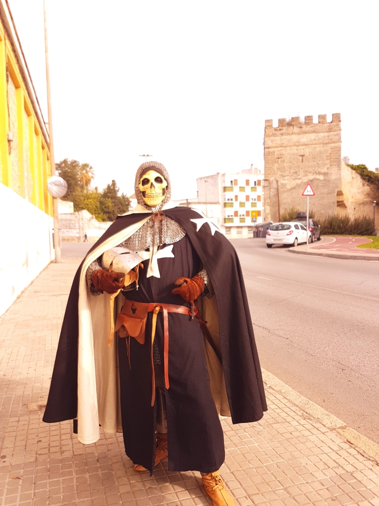 A skeleton of a knight in full armour, carrying a a helmet and a sword, posing in a modern (paved) street with part of an old medieval wall-tower fortification in the background, in broad daylight.