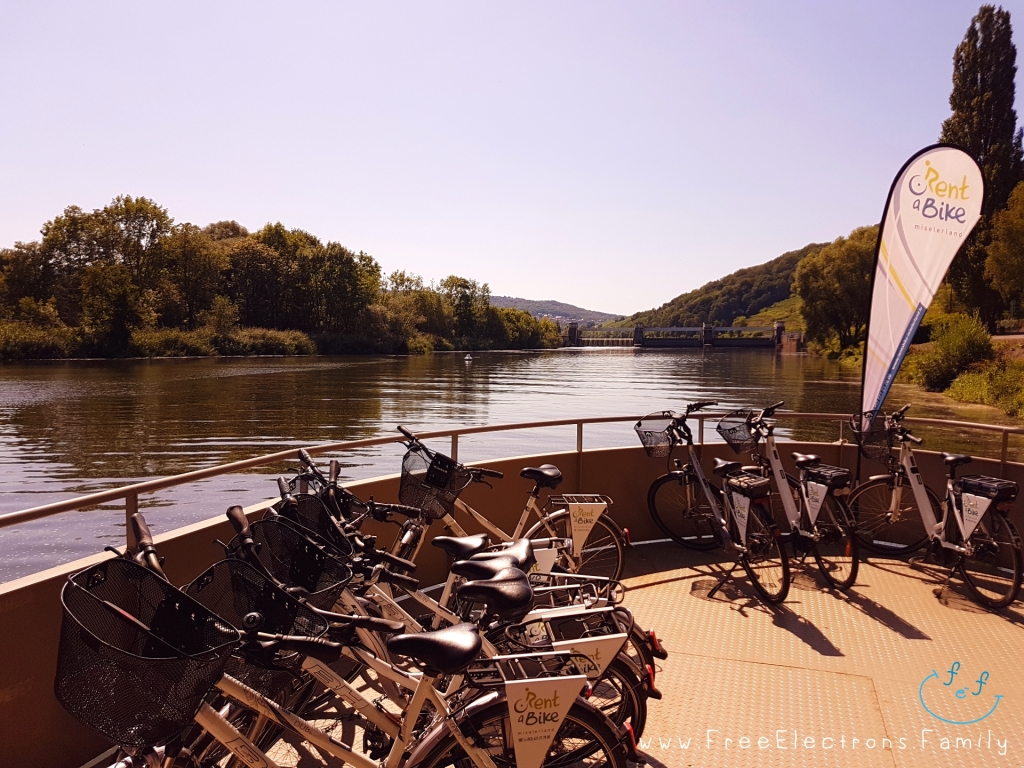 A section of pontoon with parked bicycles for rent, on a river with a buoy that marks where the Schengen Agreement was signed. . . in the distance.  www.FreeElectrons.Family
