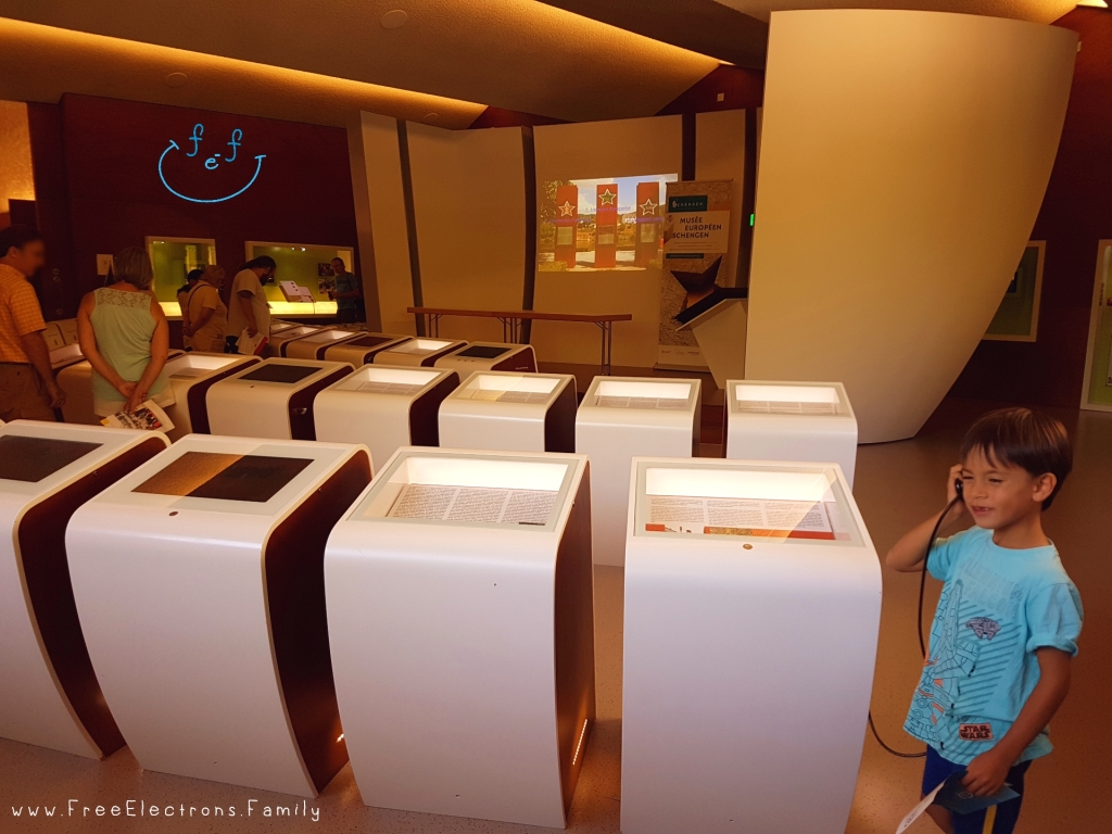 A young boy smiles as he listens to one of the interactive modules inside the European museum of Schengen.  www.FreeElectrons.Family
