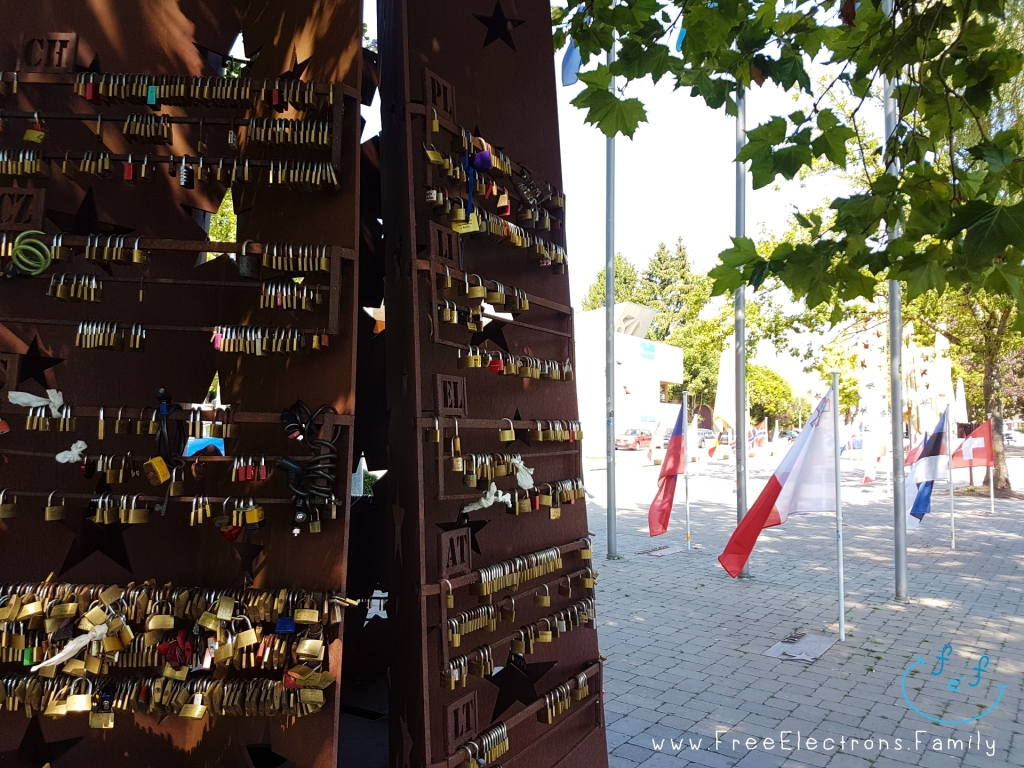 An iron monument with padlocks in a plaza with European flags.  www.FreeElectrons.Family