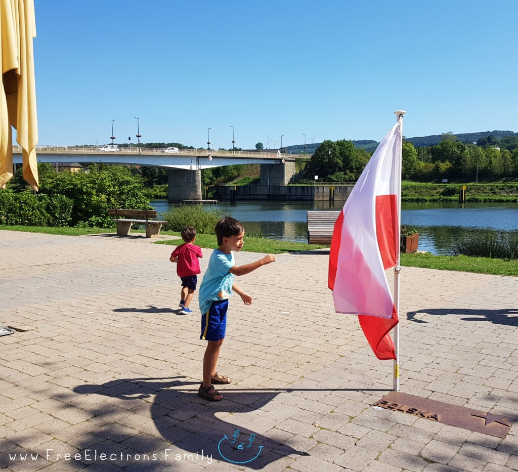 Two young boys playing in a plaza with a Polish flag; A river and a bridge in the background.  www.FreeElectrons.Family