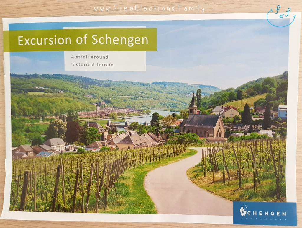 "A photo of a brochure titled ""Excursion of Schengen: a stroll around historical terrain"" with a picturesque view of small village overlooking the river and the vineyards on the other side.  Other text on picture reads: ""Schengen"" and www.FreeElectrons.Family."