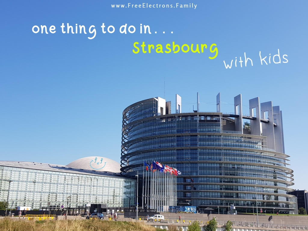 A far view of the steel-and-glass building with flags of the European Parliament.  Text reads: one thing to do . . . in Strasbourg with kids.  Other text on photo reads www.FreeElectrons.Family