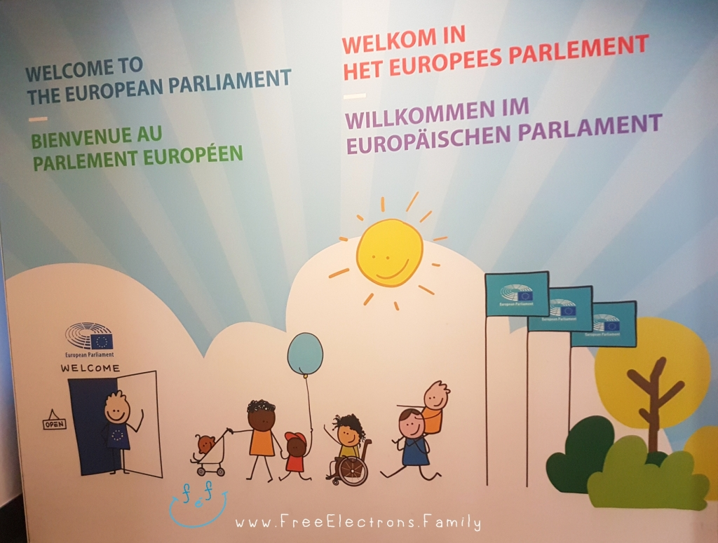 """Welcome to the European Parliament"" in 4 languages on a display board with caricature of families and children.  Other text on photo reads www.FreeElectrons.Family"