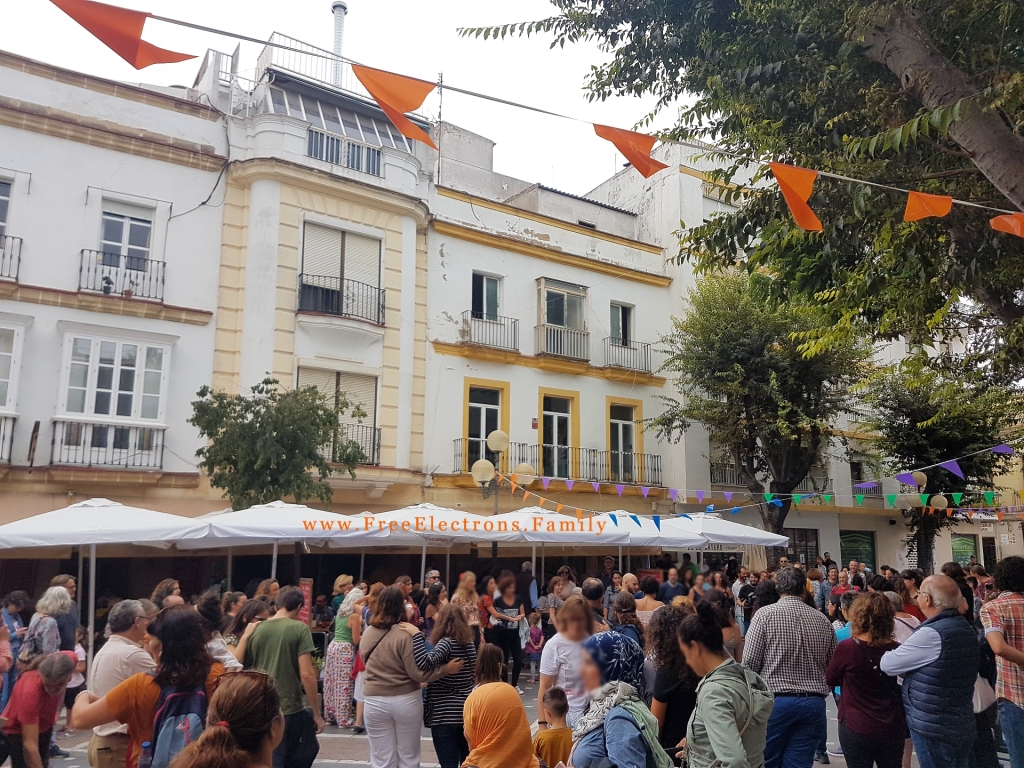 A Spanish plaza/square filled with dancing people and spectators, with 3-storey buildings with balcony and some trees in the background.  Text on photo reads: www.FreeElectrons.Family