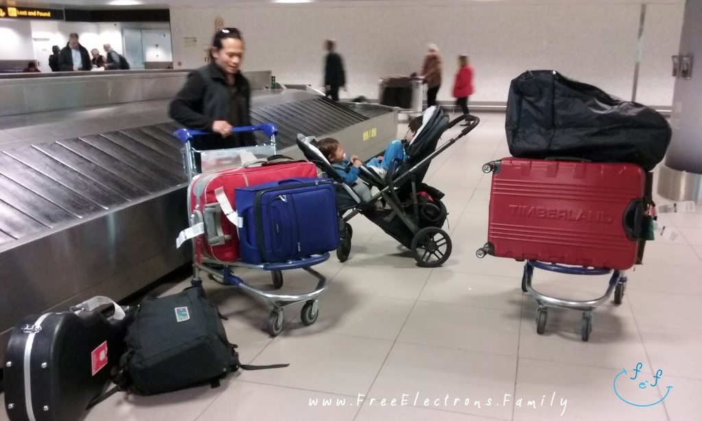 A father with 2 young kids sleeping in a stroller, picking up luggage at an airport.  Text:  www.FreeElectrons.Family
