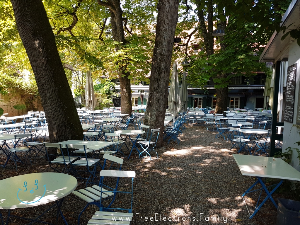 A big outdoor restaurant under shadeful trees.  Text reads: www.FreeElectrons.Family