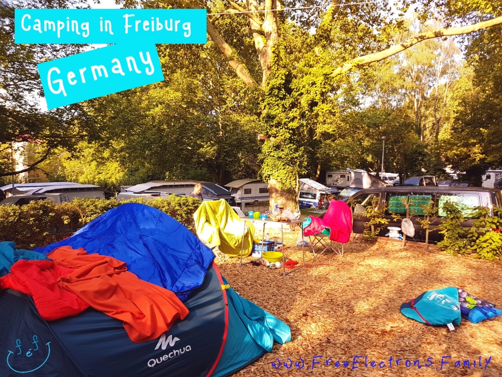 Camping pitch with a tent, tables, chairs and other stuff; camping vans and shadeful trees in the background.  Text reads:  Camping in Freiburg, Germany www.FreeElectrons.Family