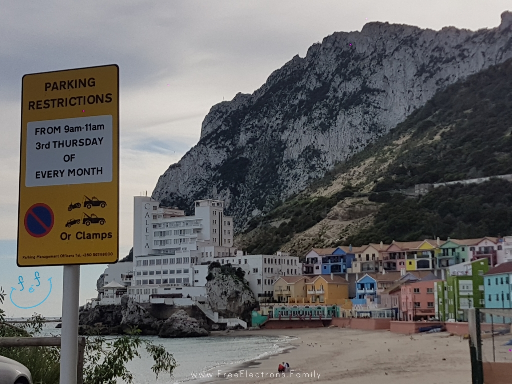 Caleta hotel colorful houses of Caleta Bay at the foot of the rock mountain of Gibraltar.  A parking signpost in the foreground.