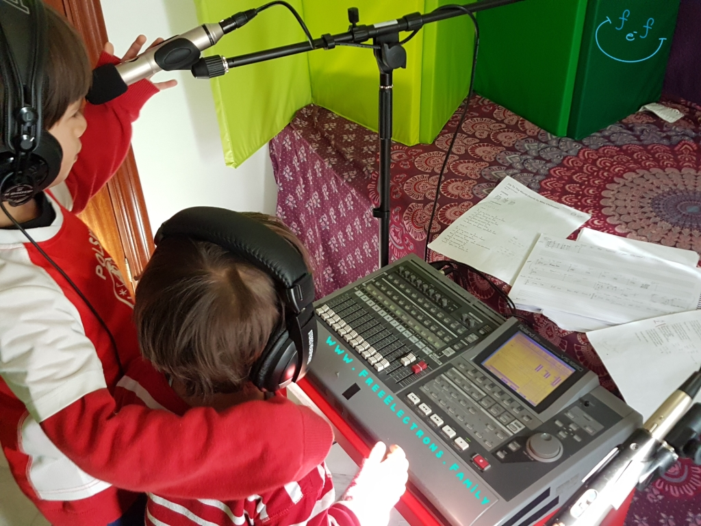 """Two young boys with headphones and microphone in front of a mobile home recording """"studio"""".  Text reads:  Joy to the World, Villancicos Mix, Rumba Flamenca Mix Spanish-English-Family Video.  www.FreeElectrons.Family"""