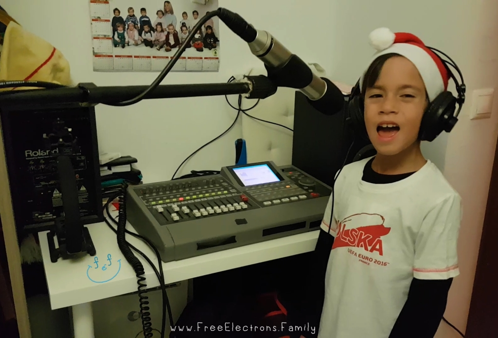 """A young boy  in a white """"Polska"""" shirt with a Santa Claus hat and headphones on singing in front of a microphone in a home recording studio.  www.FreeElectrons.Family"""