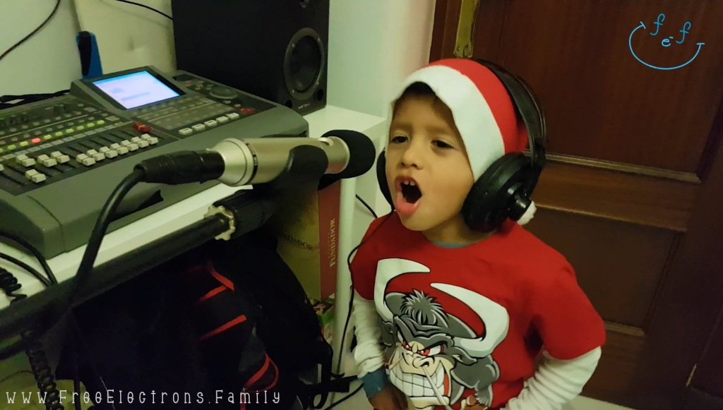A young boy in a red shirt with a Santa Claus hat and headphones on singing in front of a microphone in a home recording studio.  www.FreeElectrons.Family