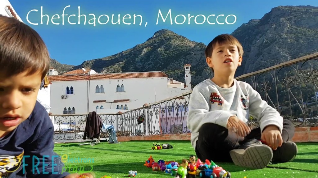 Two young boys with their toys on a balcony in Morocco with the Chefchaoeun mountain peaks behind them. -Free Electrons Family