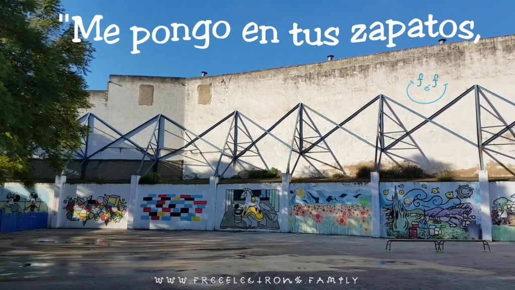 """An outdoor patio with various paintings on the walls.  Text reads in Spanish, """"Me pongo en tus zapatos"""" (I put myself in your shoes).   www.FreeElectrons.Family"""