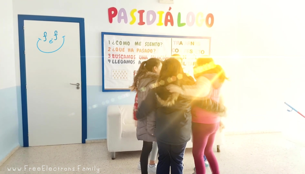 """Children in a circle with arms around each other.  a sunray obscures their faces.  A sign reads, """"Pasidialogo!"""" www.FreeElectrons.Family"""
