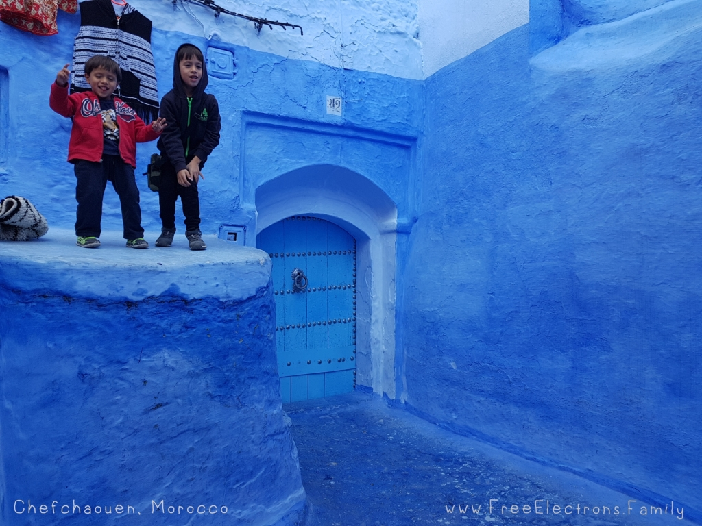 Two smiling young boys at a doorstep in Chefchaouen, Morocco where almost everything is blue.-Free Electrons Family