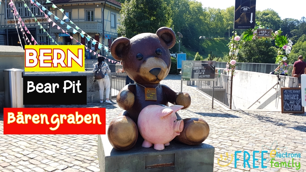 "A monument of a brown bear with a pink pig.  Text reads: ""BERN Bear Pit Barengraben.""  www.FreeElectrons.Family"