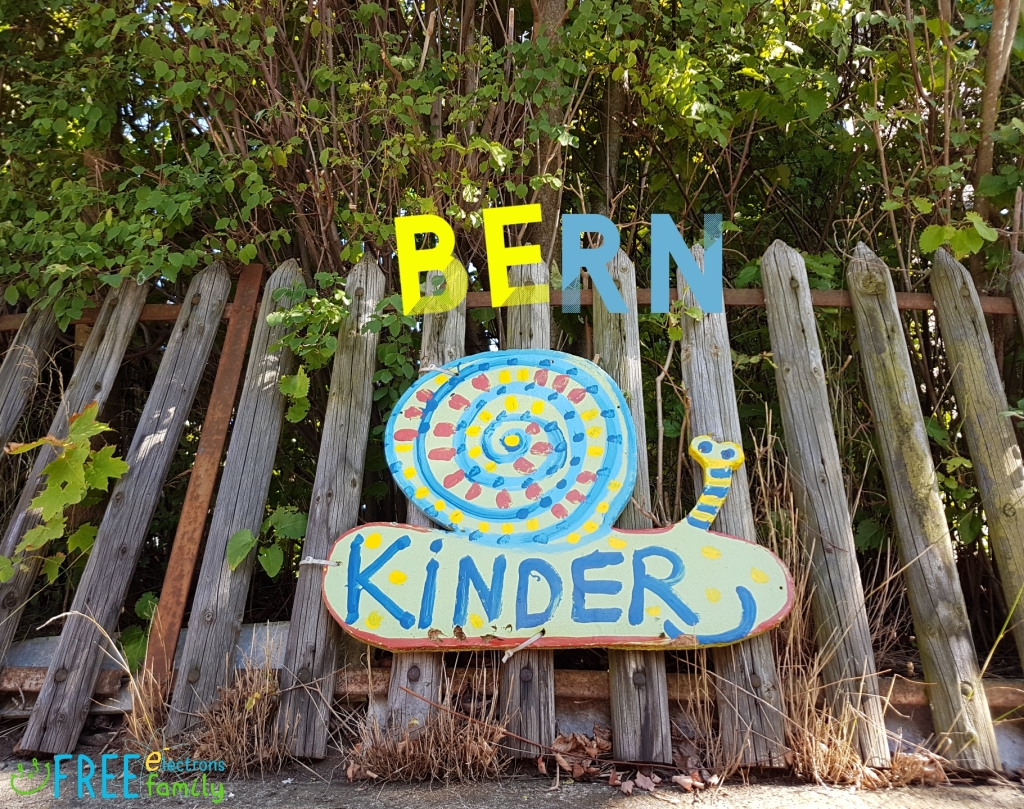 "A rustic fence with overgrown vegetation and a made-up sign in a form of a snail that reads ""Kinder"", with ""BERN"" super-imposed in different colors to read ""Be Kinder!""  www.FreeElectrons.Family"