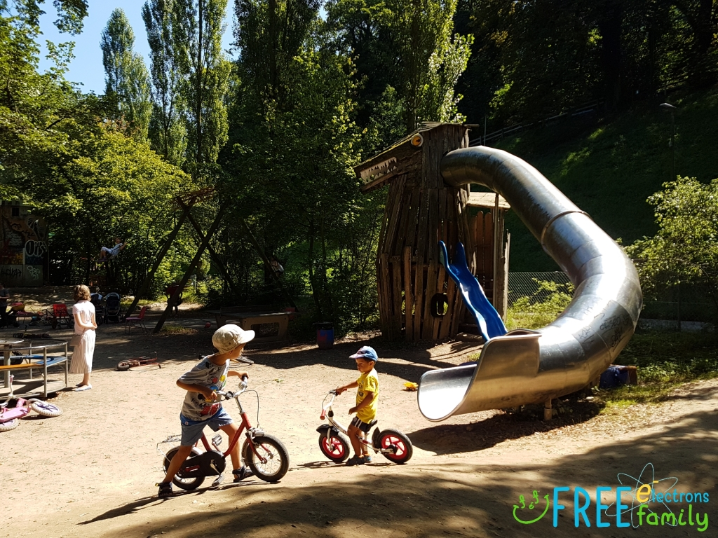 Young children on bicycles with a homemade dragon-slide at the Spielplatz Längmuur playground in Bern, Switzerland. www.FreeElectrons.Family