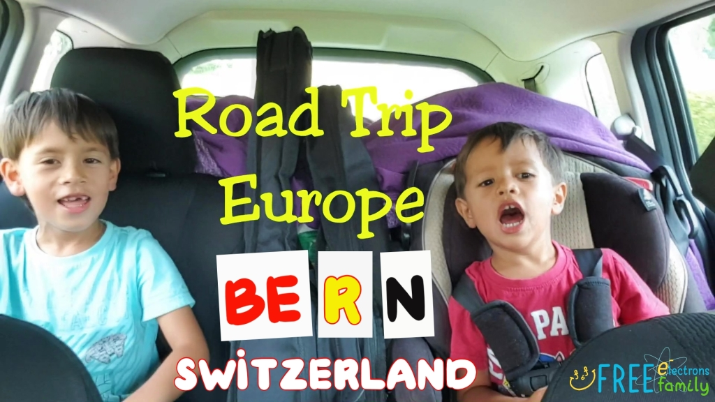 Two young children in a car, cheering, smiling.  Text reads: Road Trip Europe Bern, Switzerland. www.FreeElectrons.Family
