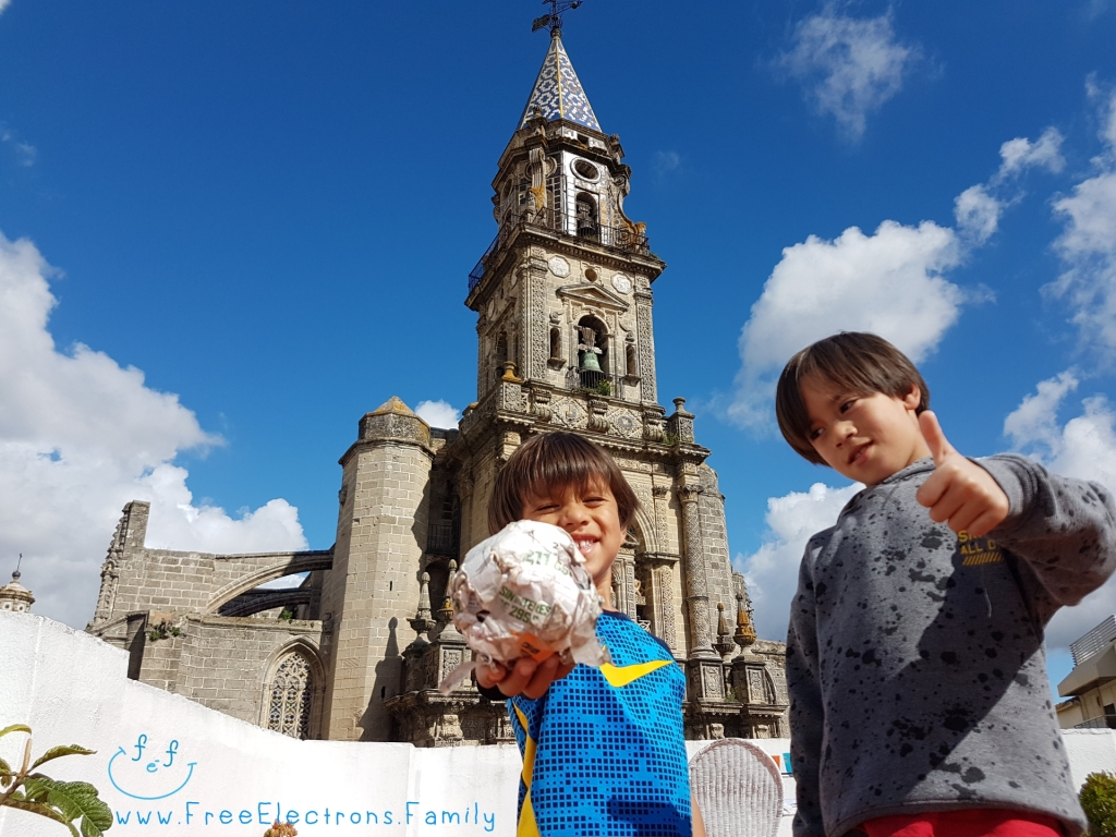 Two young kids on a rooftop, smiling and holding a paper football with an old church in the background under bright blue sky. www.FreeElectrons.Family