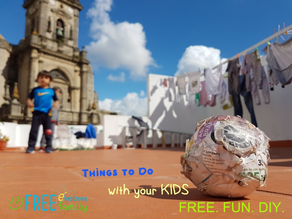 Paper football on a rooftop with 2 kids and an old church faded in the background under blue sky. ~Free Electrons Freeplay
