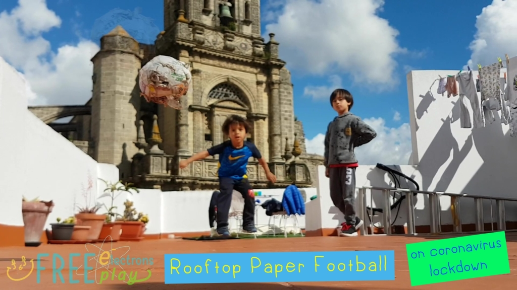 Two young kids on a rooftop, playing paper football with an old church in the background under bright blue sky. ~Free Electrons Freeplay