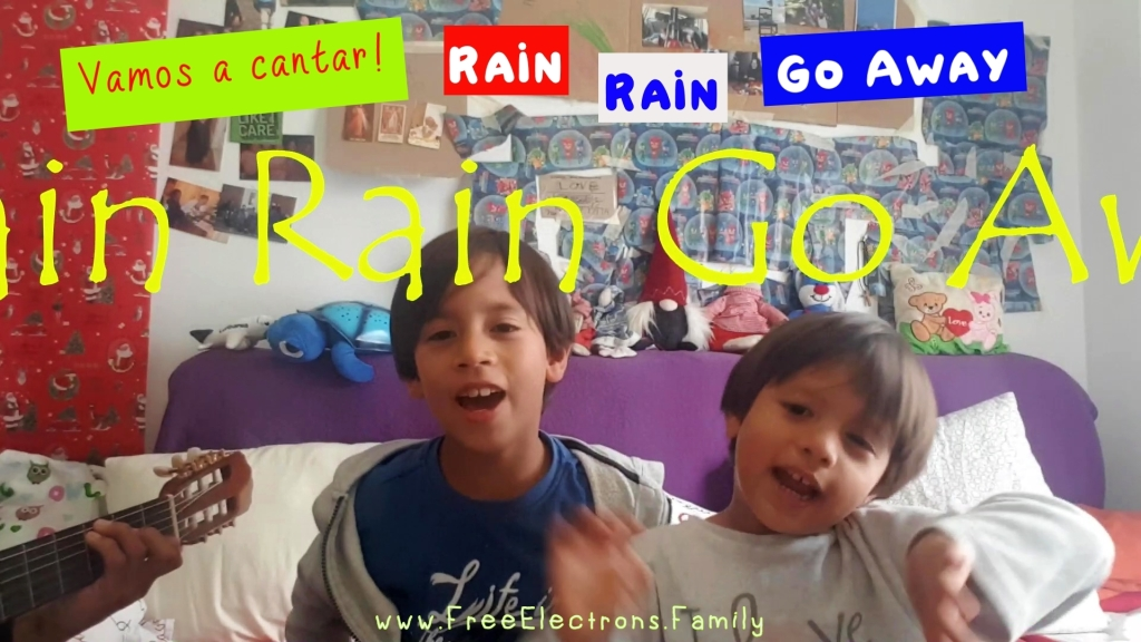 Two young kids singing in bedroom to a father's acoustic guitar playing.  Text in picture reads: Vamos a cantar! Rain Rain Go Away.