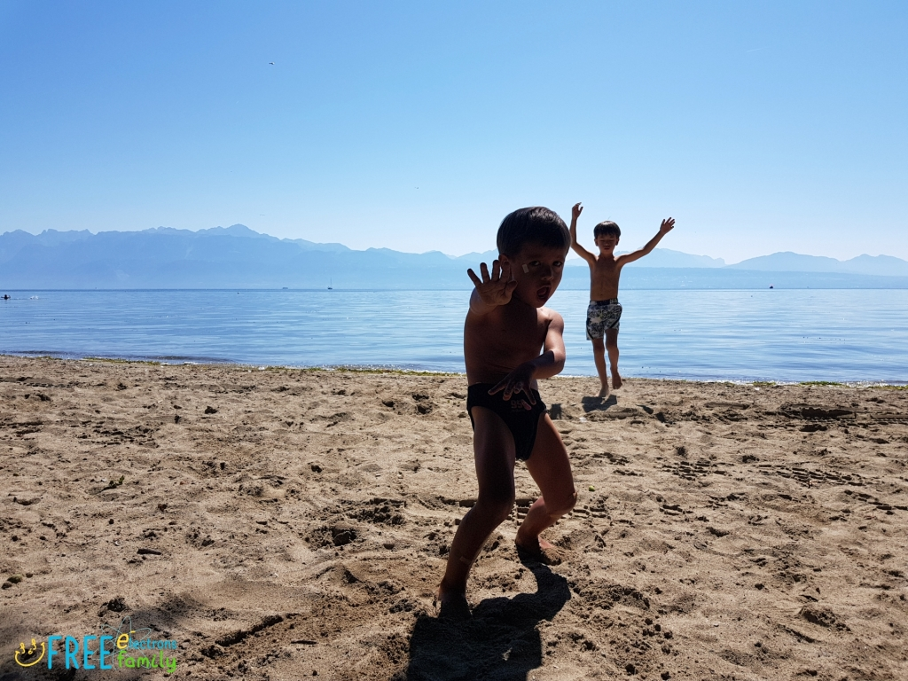 Two young boys dancing/playing on the beach of Lake Geneva in Lausanne, Switzerland, with the Swiss alps in the background.  www.FreeElectrons.Family