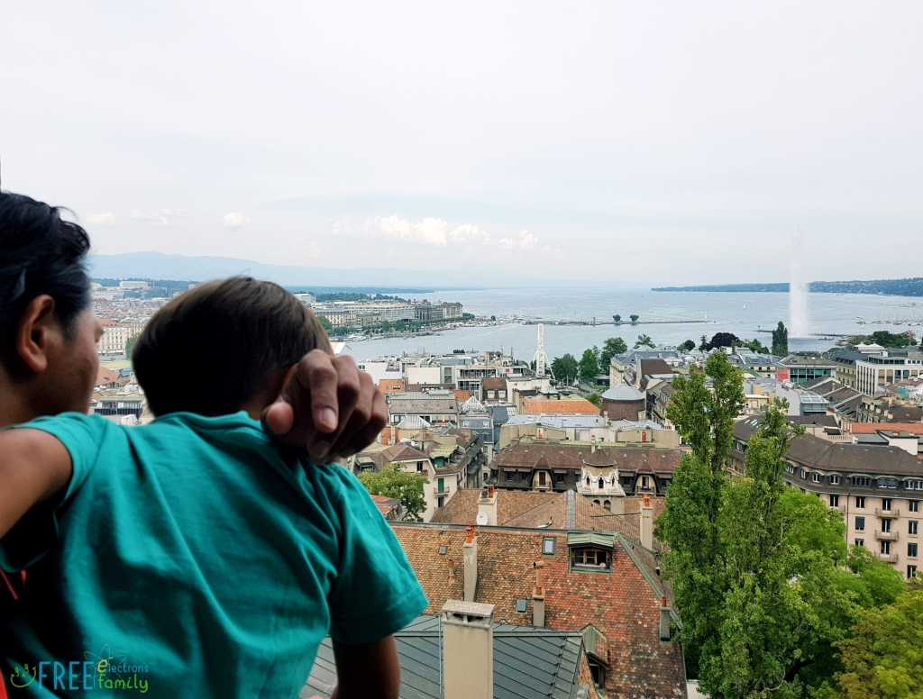 A father carrying son, both looking at Geneva's lakeshore from the high viewpoint of a Cathedral tower.   www.FreeElectrons.Family
