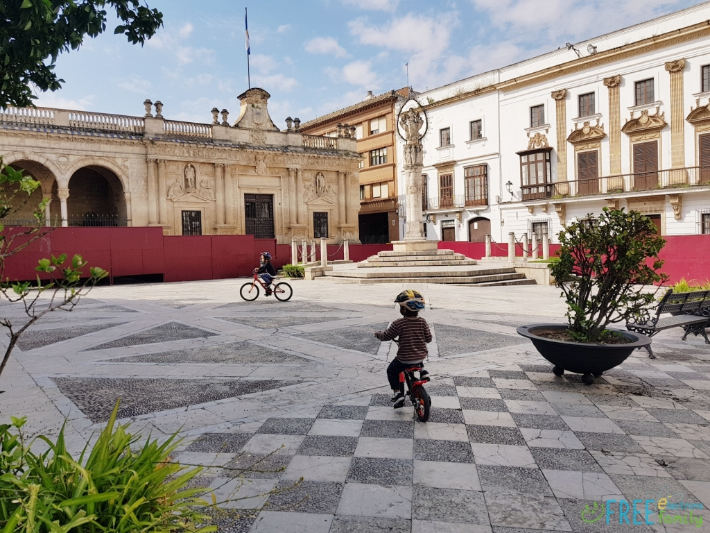 Two young boys on bicycles on a square, Plaza Plateros, Jerez de la Frontera during coronavirus lockdown in Spain.  www.FreeElectrons.Family