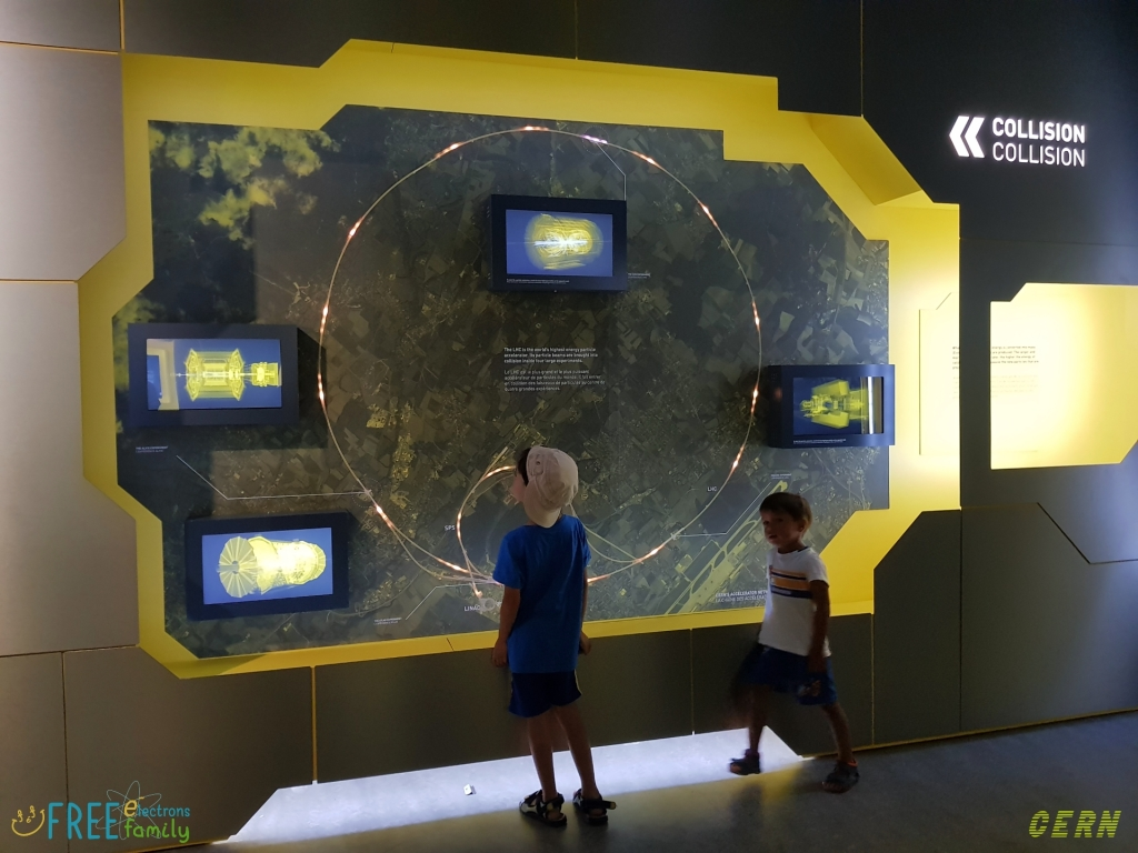 Two young children in front of a wall-sized map, showing an illustrative bird's eye view of Geneva and the outlying towns in both Switzerland and France around which the Large Hadron Collide goes.  #FreeElectrons.Family