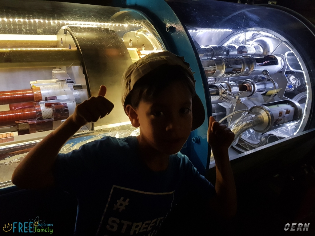 A young kid poses with thumbs up in front of a model of the Large Hadron Collider at CERN's microcosm exhibit.   #FreeElectrons.Family