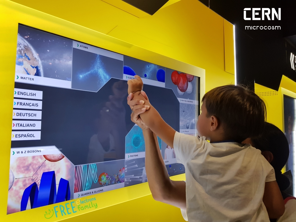 A young kid, carried by a parent, interacting with an informative touch screen in CERN's microcosm exhibit.   #FreeElectrons.Family