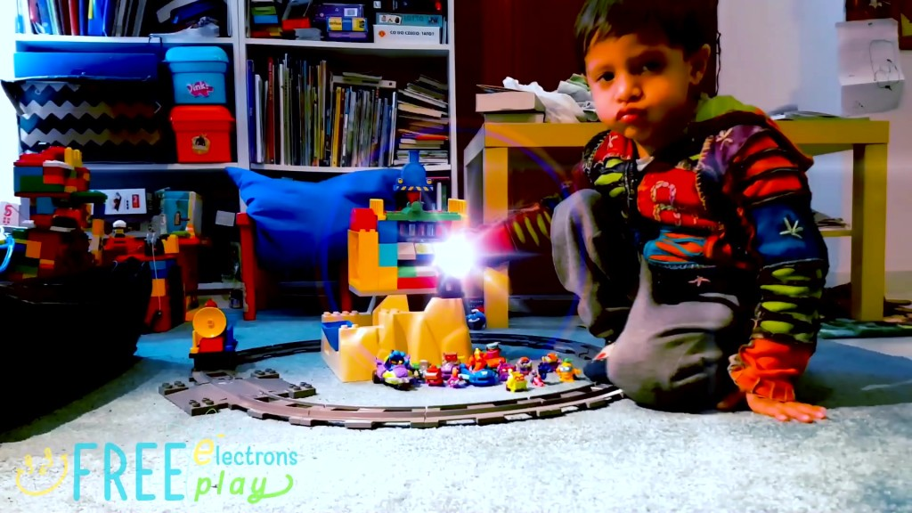 A young child playing with on the carpet with SuperZings with Lego Duplo toys with special flash effect. -Free Electrons FreePlay