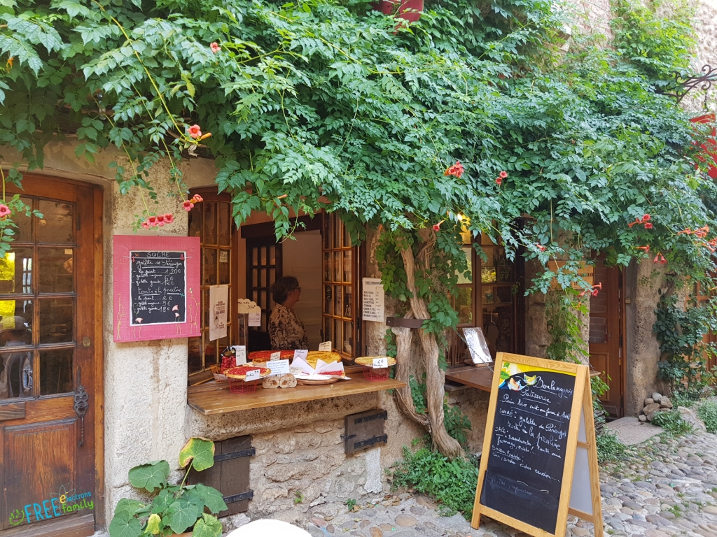 A small shop with fully grown vines overhanging windows open and offering pizzas and other foodstuff with blackboards listing names and prices.