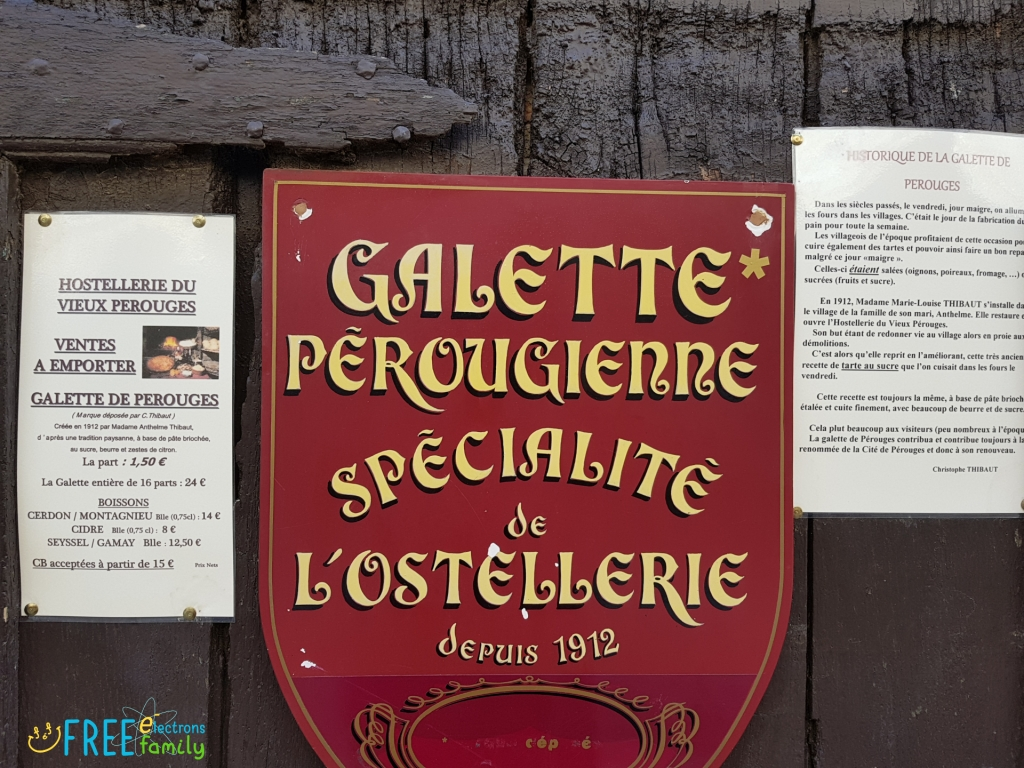 "An advertisement sign that reads ""Galette Perougienne Specialite de L'Ostellerie depuis 1912."""