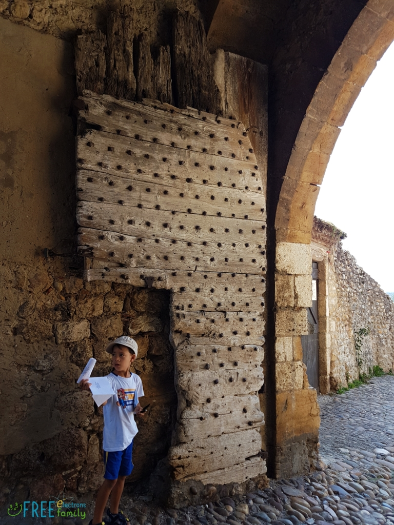 A young boy, looking away, holds a white paper by the broken wooden gate, under a stone archway entrance of a cobblestone village.  www.FreeElectrons.Family