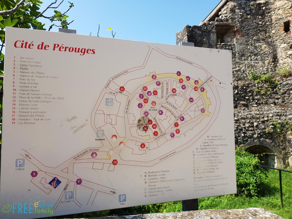 A map of the Cite de Perouges with part of a stone house in the background, grass and blue sky.