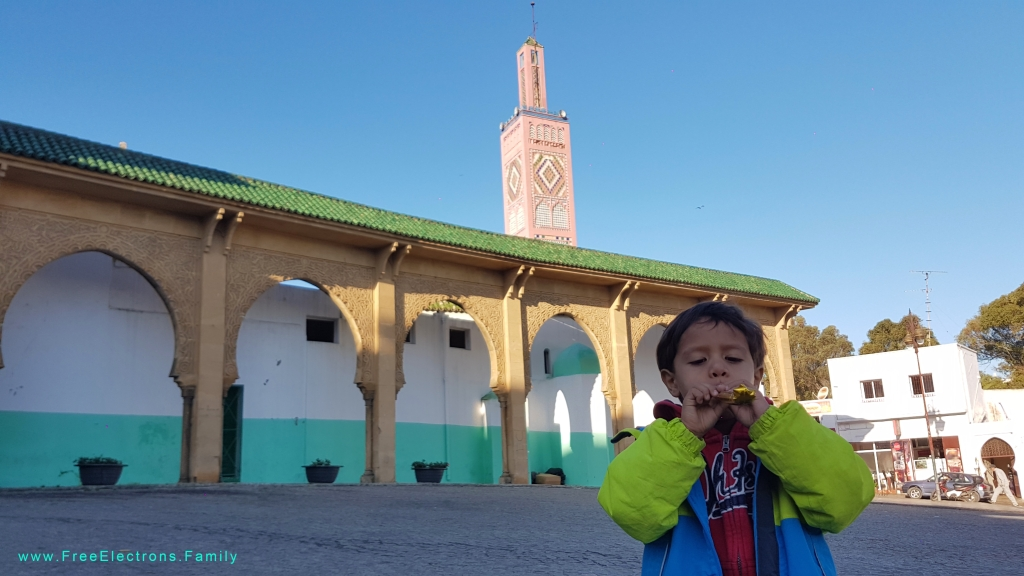 A young boy with a whistle in a market square with a mosque tower in the bacground.