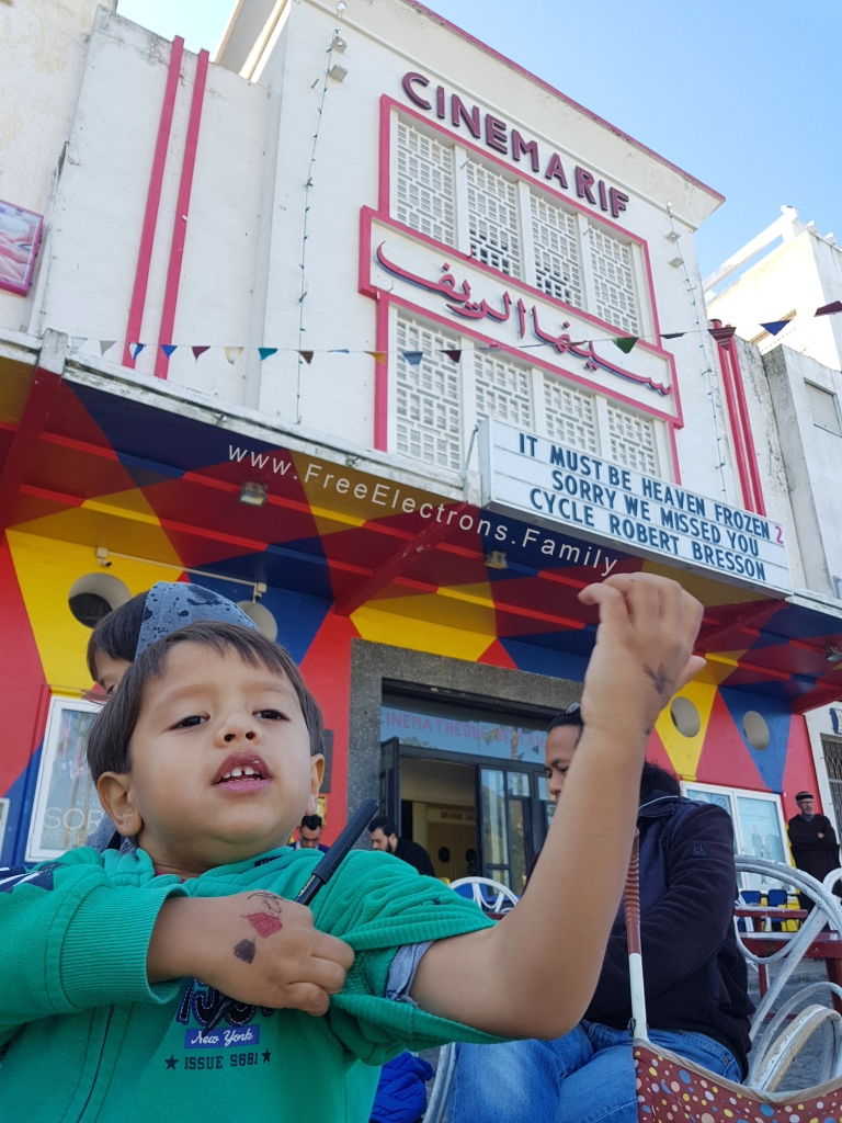A young boy showing ink drawings on his arm/hands with an old movie theater in the background.