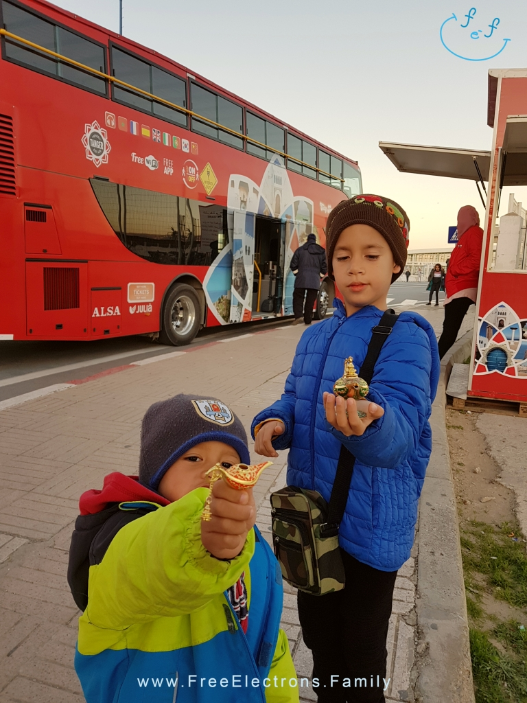 Two young boys in winter clothes show off their little souvenirs in front of a red double-decker bus.
