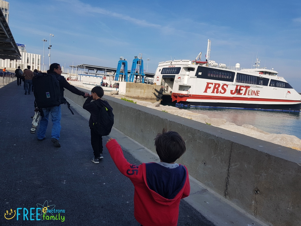 A father and two young boys  with backpacks heading towards a ferry.