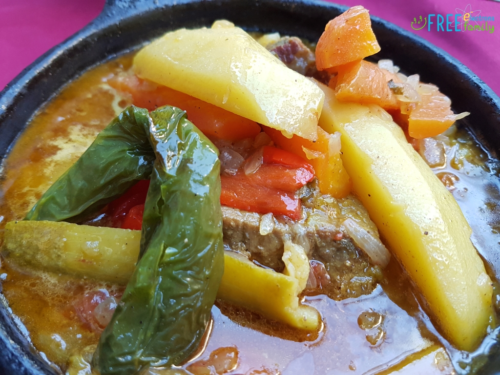 Soupy beef and vegetable dish with green pepper, potato, carrots, rice, beef and tomatos.