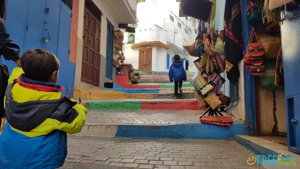 Two young boys walking uphill in a colorful and quiet street of Morocco.